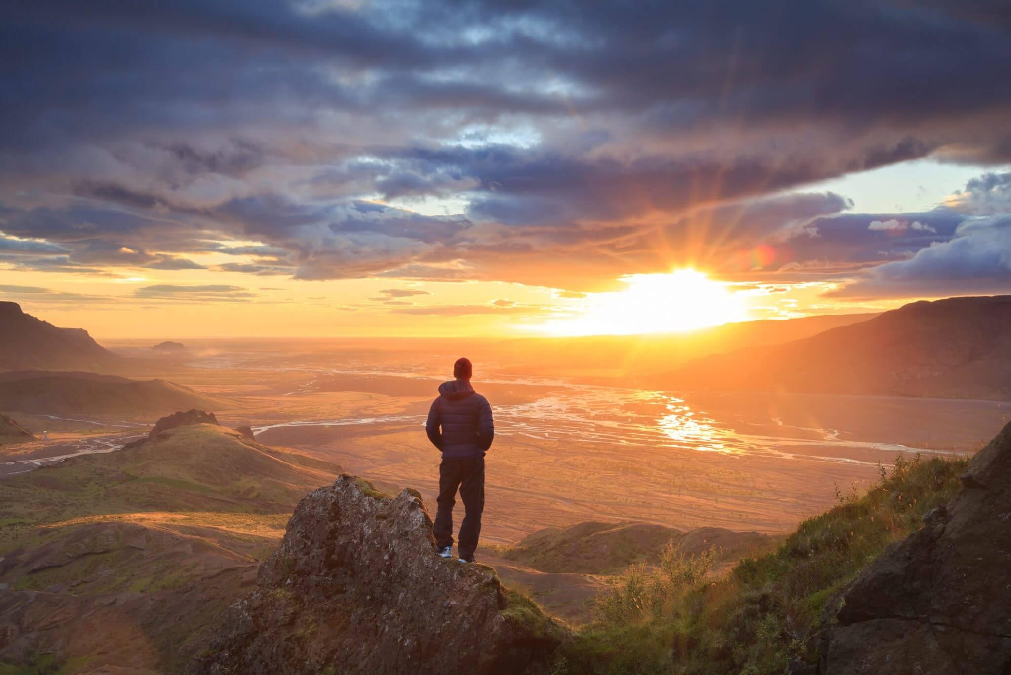 Personne debout devant un couché de soleil : devenir un leader inspiré